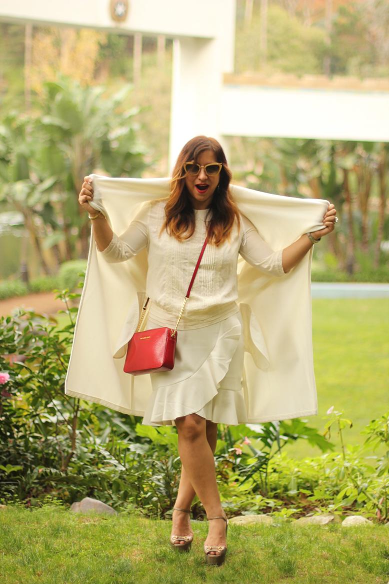 Rossana Vanoni fashion blogger at Lake Shrine wears white coat, blouse and skirt